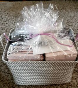 (312) Women's Spa Basket 1 Floral. Includes: $40 Massage gift certificate, electric wax warmer, mini back pack, bath wrap and headband, lotion, shower gel, candle, storage basket, glitter pen set, fountain, travel mug, foot lotion and socks, purple blanke